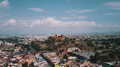 Aerial footage of church built on top of a pyramid by the Spanish in Cholula, Puebla. You can see the base of the pyramid, the church and the city in the background.