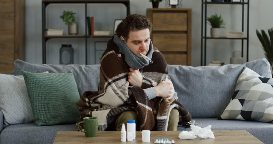 Unwell caucasian man covered with a warm plaid measuring a temperature and having a thermometer in his mouth, shaking as having a fever and a flu. At home. Inside