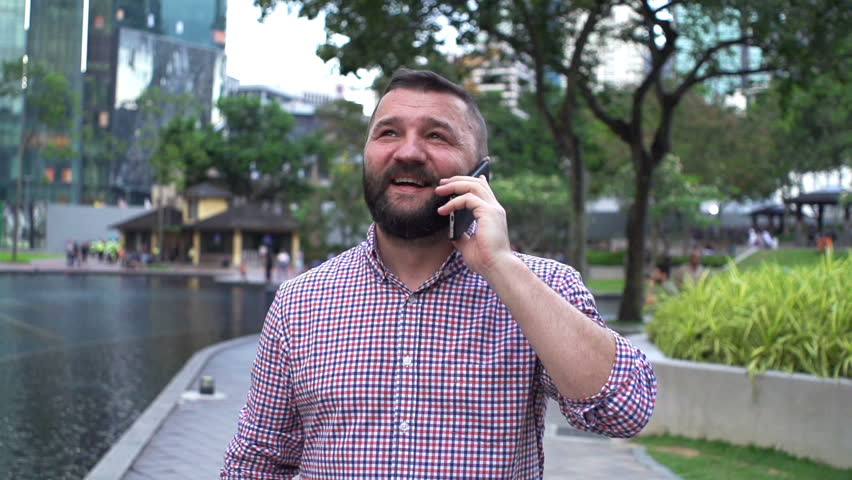 Young man talking on cellphone while walking by fountain in city, super slow motion 120fps    Shutterstock HD Video #1010504465