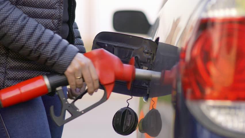 A woman runs a gasoline car at a gas station. Close-up.