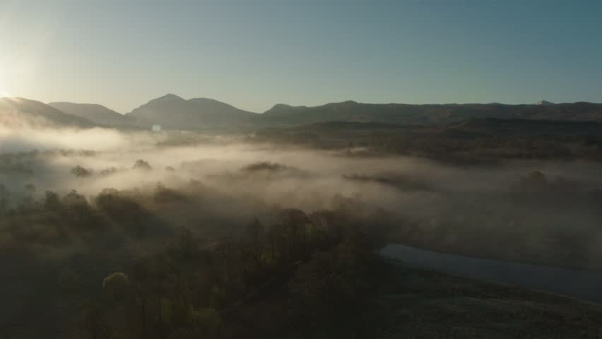 Low hanging mist over tree's near Kilchurn castle, Scotland