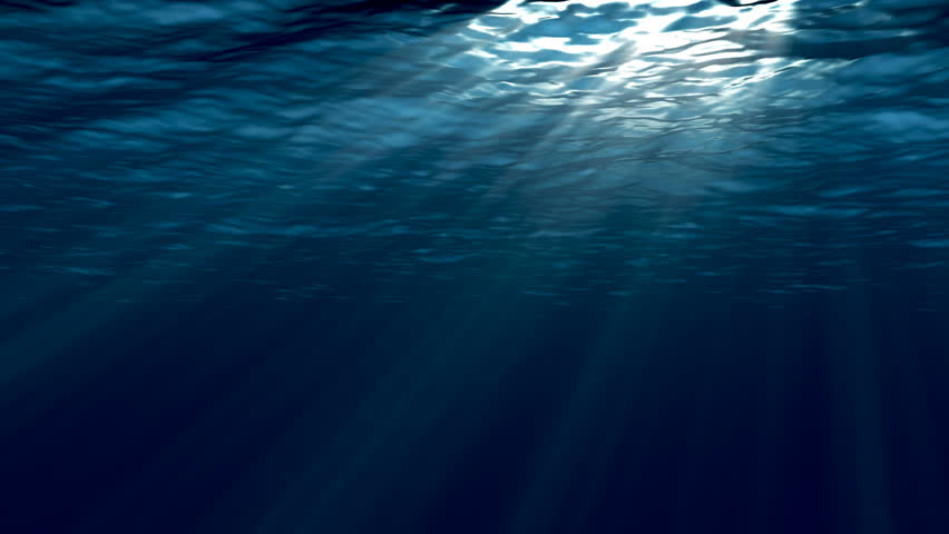 Dark blue sea surface seen from underwater.  Abstract waves underwater and rays of sunlight shining through.  #1010518235