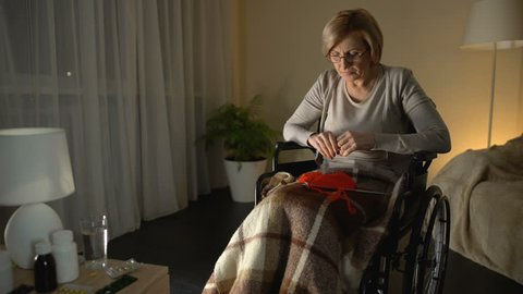 Woman in wheelchair suffering from parkinsonian tremor, helplessness in old age