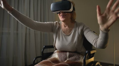 Excited senior lady in wheelchair having fun in modern virtual reality headset