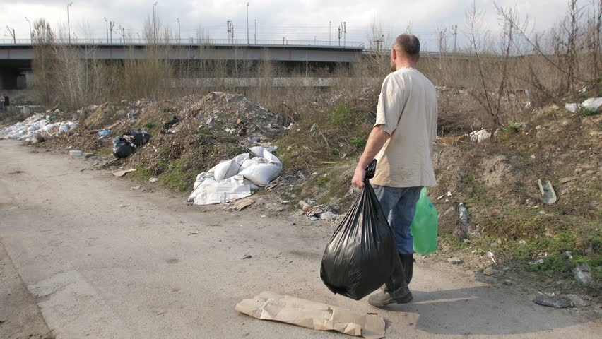 Back view full length homeless male walking along trash landfill site with trash bags in hands, scavenging for material to recycle. Homelessness and pollution concept. Steadicam shot