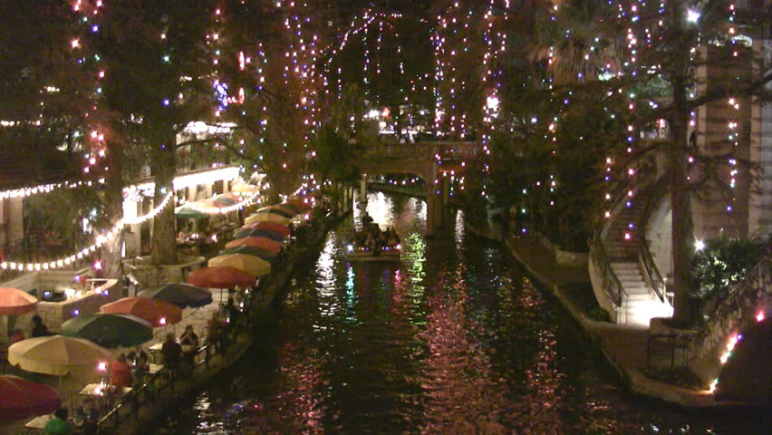 Video night Christmas lights of the San Antonio Texas Riverwalk. Tourists walking by restaurants and shops. Vacation area. Bright lights and festive holiday atmosphere. Foot bridge in distance.