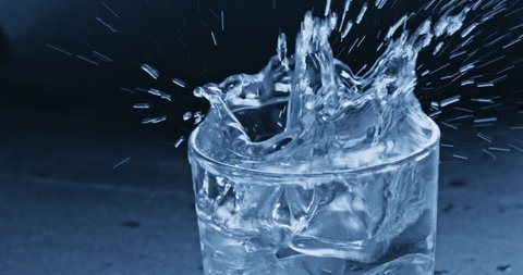 Two ice cubes fall into a glass with water creating splashes. Slow motion 2k video shooted on 240 fps