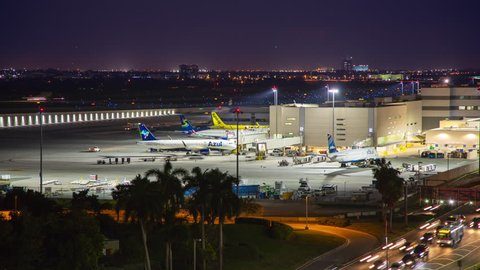 Ft. Lauderdale, FL - 2018: Hollywood FLL International Airport Terminal 4 Exterior Night Timelapse with Commercial Jet Airliners parked at the Concourse Gates in a Vibrant Dusk Setting
