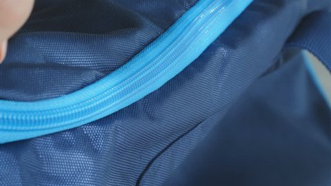Macro close-up shot of a bag's zipper being opened and closed by female fingers, slow motion