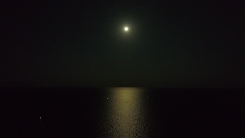 Aerial night footage moon over ocean