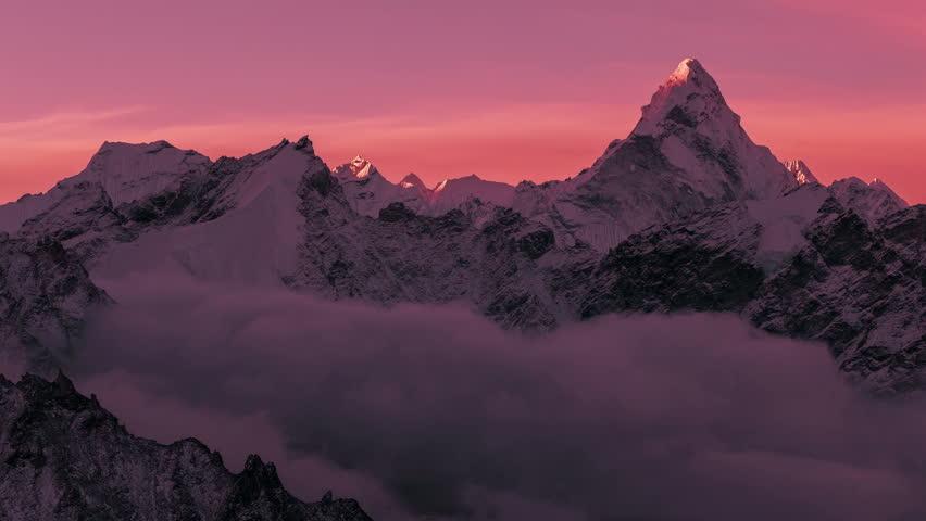 Greatness of nature concept: grandiose view of Ama Dablam peak (6812 m) at sunrise. Nepal, Himalayan mountains. Time lapse panorama.