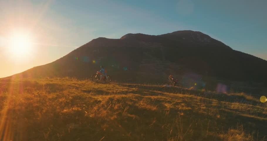 Tracking shot of friends pushing their bikes to the top of the mountain in beautiful sunset light. | Shutterstock HD Video #1010578205
