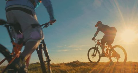 Two mountain bikers reaching the top celebrating with high five in beautiful evening light.