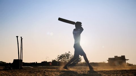 A slow motion shot of a young boy standing against the sun playing cricket match hits the ball for six . A silhouette shot a confident young man or batsman hits the cricket ball in the sky with bat.