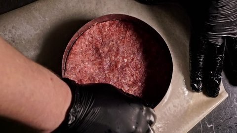 Cook makes meat medallions for burgers. Chef in black food gloves makes cutlet. Cutlets are leveled in steel ring in an even medallion. On top of pouring spices pepper and salt.