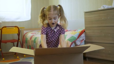 Girl opens the parcel from the online store. Child looks in the box, is surprised and happy to receive a surprise. Little Girl opened a box with a gift. Slow Motion.