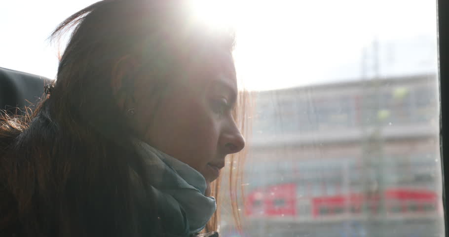 Woman riding train commuting to work or study. Girl looking out train window starring at landscape view passing by | Shutterstock HD Video #1010606285