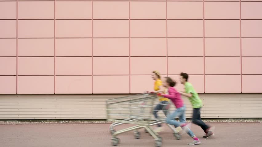 Happy family with shopping carts in a parking lot near a supermarket. People running and engaged in purchases in shopping centre. Mom, Dad, Children having fun outdoors with shopping trolleys race. | Shutterstock HD Video #1010611145