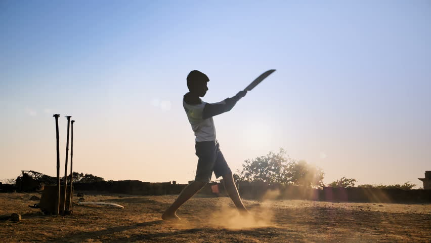 A young boy batting hits the cricket ball for a six in a open field of Indian village. A slow motion shot of a young teenager playing cricket against the sun strikes the cricket ball hard