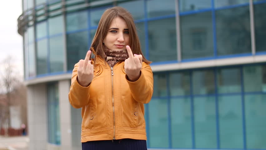 Very beautiful girl makes obscene hand gesture by showing middle finger in the city. Outdoor, urban landscape