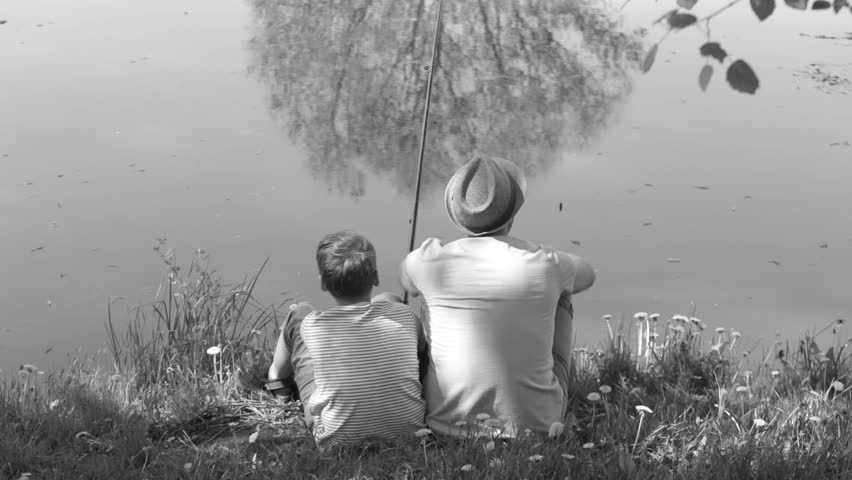 Black and white video of happy family on summer vacations concept. Father and son fishing together at river bank.
