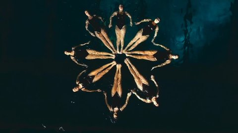 group of synchronized swimmers performing underwater
