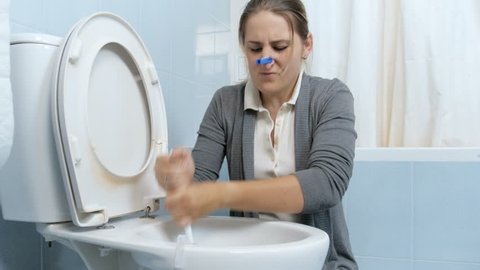 4k footage of young woman closes her nose with clothespin before cleaning stinky stained toilet