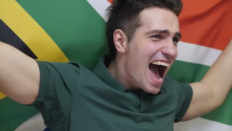 South African Young Man celebrating while holding the flag of South Africa in Slow Motion