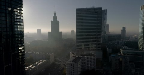 Drone footage of Warsaw city center focus on skyscrapers and Palace of Culture and Science. Shot is taken during a misty but sunny day in Polish capital city.