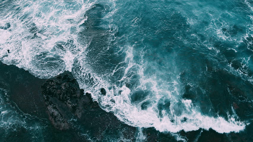 Abstract aerial view of ocean waves crashing on rocky shoreline