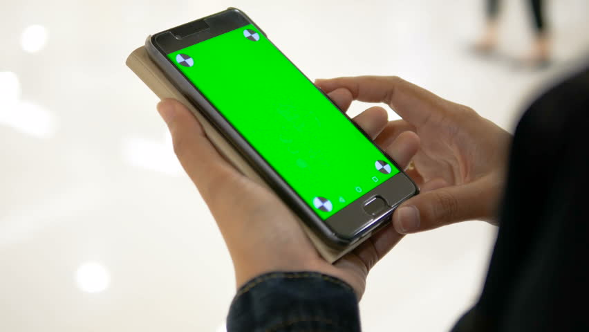 Hands of woman holding smartphone with green screen and tracking mark | Shutterstock HD Video #1010696345