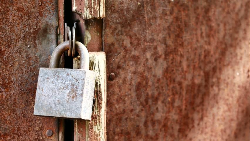 Closeup of old lock on red metal garage door. Rusty lock on an old wooden gate.