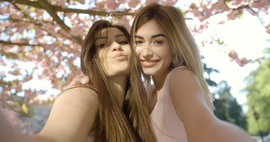 b12246de Portrait of the charming blonde and brunette girl friends with pretty smile  hugging and taking selfies in the blooming sakura garden. 4k footage.
