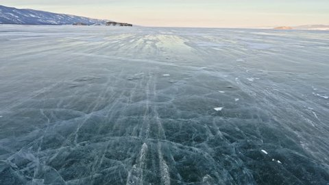 Snow is flying over surface of ice. Snowflakes fly on ice of Lake Baikal. Ice is very beautiful with unusual unique cracks. Background view mountain landscape.