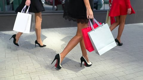 Legs of shopaholics with shopping bags walking down mall. slow-motion. beautiful female legs. close-up of female legs in high heels. shopping girl. shopping girls. with shopping bags walking, friends