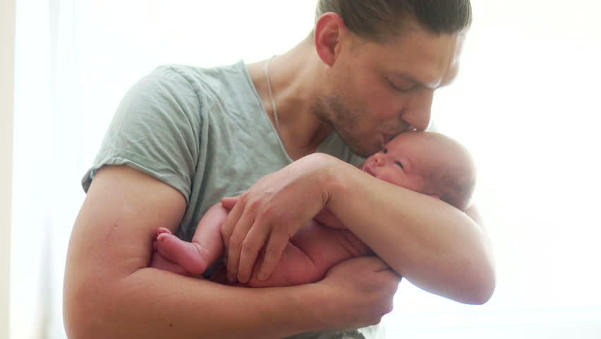 A young father holds a newborn baby in his arms and kiss him. Father's Day. Happy fatherhood, the birth of a new life