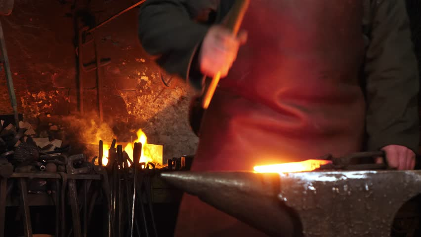 The hands of smith beat on glowing hot metal and sparks fly in all directions