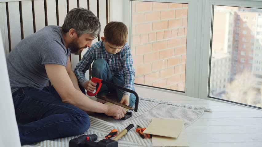 Little boy is focused on sawing piece of wood with hand saw with his father helping and teaching him. United family, construction work and childhood concept. | Shutterstock HD Video #1010801105