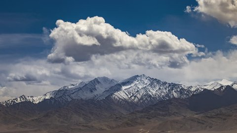 Aerial view of high snow mountain range on rural desert landscape with beautiful blue sky and amaizing cloud moving as background, Leh, Ladakh, India.