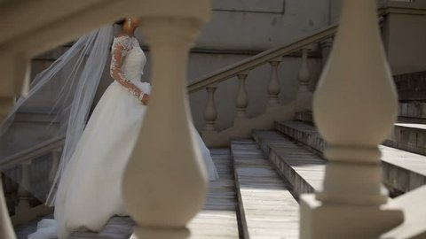 Bride in wedding dress with veil goes up the stairs. The Bride Walks. Beautiful model girl in a white wedding dress. Female portrait of cute lady.