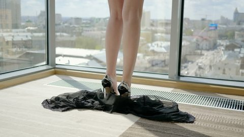 Close-up of female slender legs in high-heeled shoes and black negligee falling on the floor. 4K