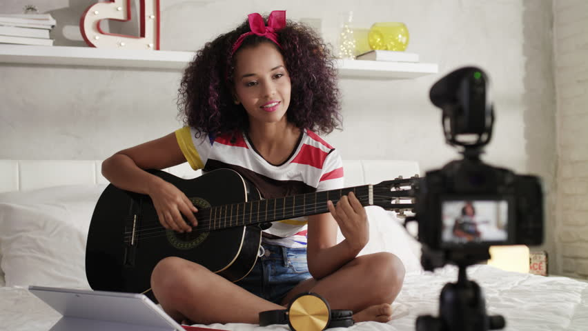 Happy black girl at home playing guitar. Young African American woman working as web influencer, recording vlog and music tutorial for the Internet. | Shutterstock HD Video #1010832905