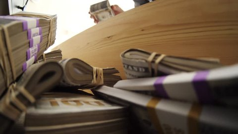 Funny absurd video concept of a man hiding his money inside a wooden drawer.