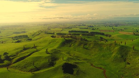 Aerial view of north island of New Zealand, picturesque lush green hills of Shire/Hobbiton (The Lord of the Rings and Hobbit location), fantasy landscape at sunset time, 4k UHD