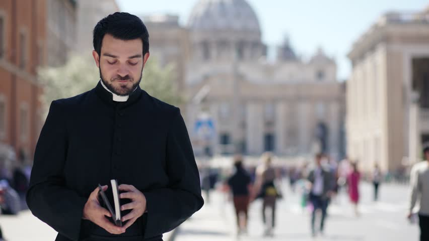 Portrait of bearded Catholic priest scrolls the Bible and smiles at the camera | Shutterstock HD Video #1010837735