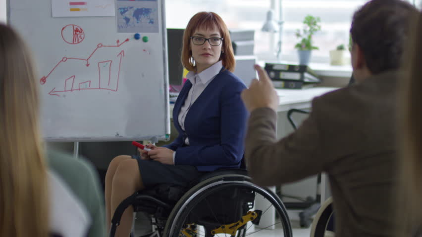 Tilt up of paraplegic businesswoman in wheelchair answering questions of group of employees and explaining graph on flipchart during business training