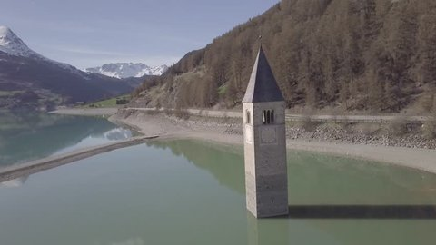 Aerial view of Bell tower in the Resia Lake, Italy, 4k, dlog