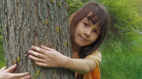 A child is hugging a tree. A little girl hides behind a tree.