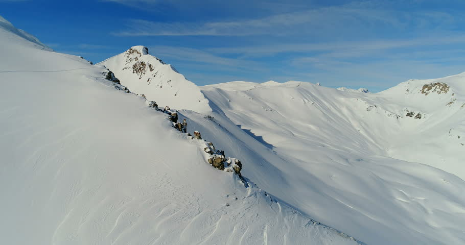 An aerial view over snowy rocky ridge in the winter of the alpine mountains, Livigno crest