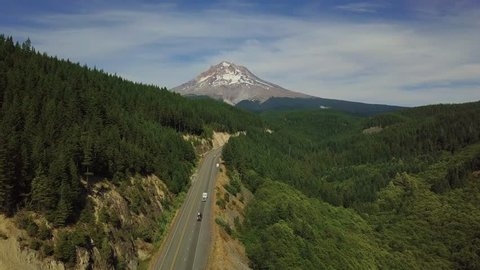 Cars driving along the road in Mt. Rainier National Park with the Mount Rainier in the distance
